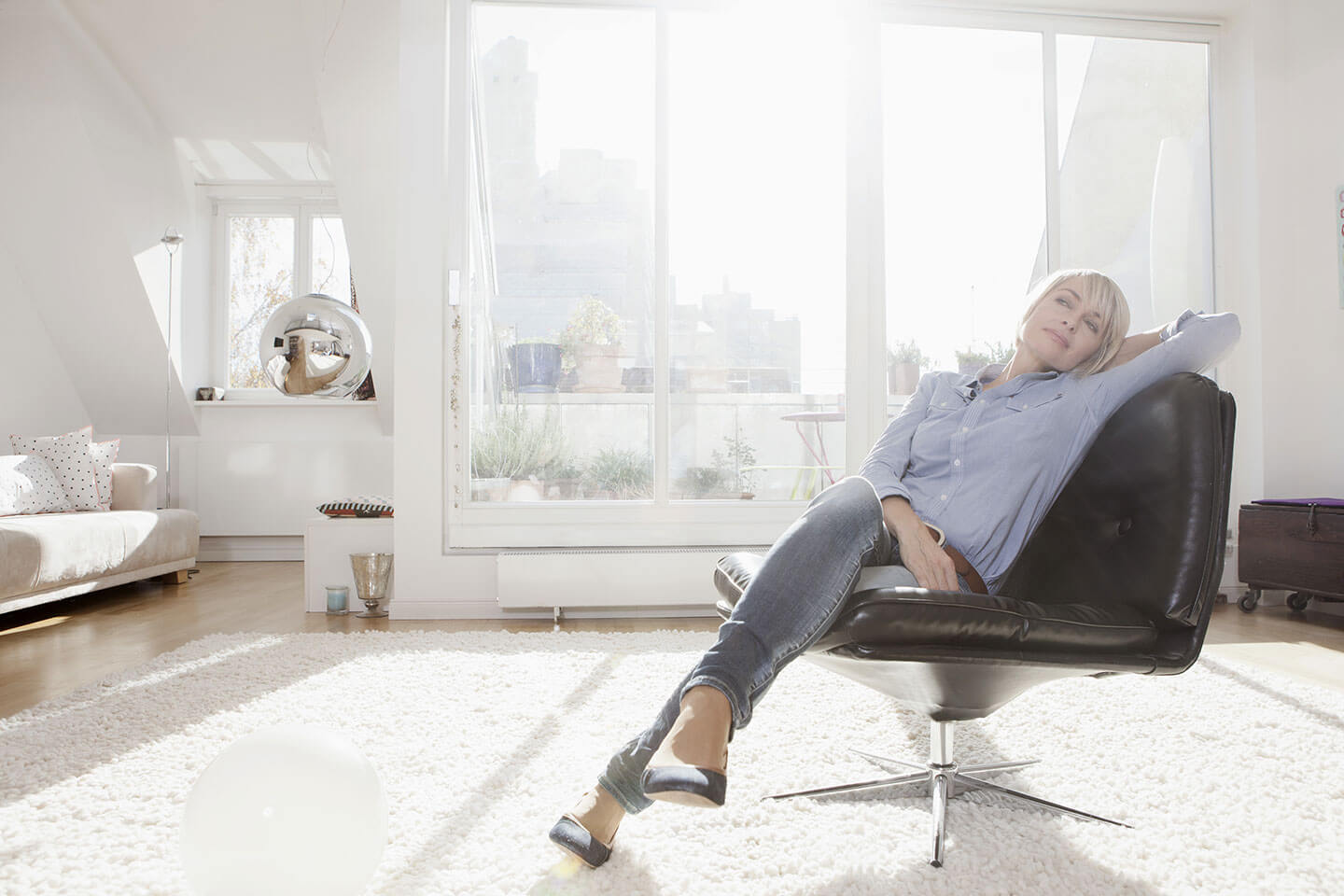 A woman relaxing on a black chair in a white living room