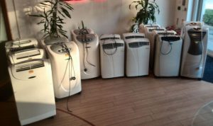 Several white unplugged air conditioning units in a room